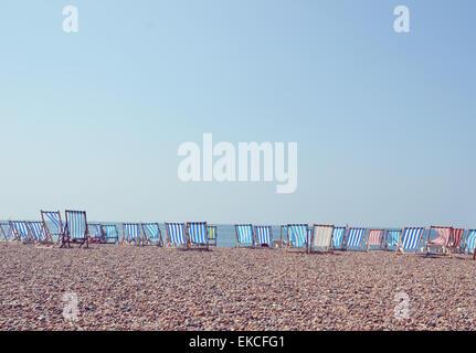 Deckchairs in a row on Brighton Beach, UK - Stock Photo