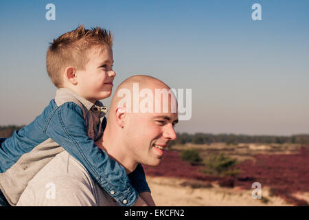 Father giving his son a piggyback - Stock Photo