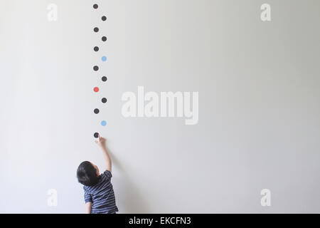 Boy trying to pick one of the dot patterns off the wall - Stock Photo