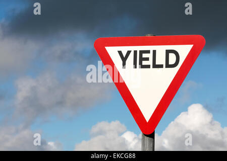 Give way sign with text yield and dark clouds in Ireland - Stock Photo