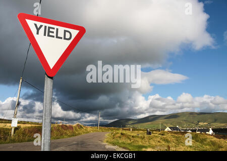 Give way sign with dark clouds in Ireland - Stock Photo