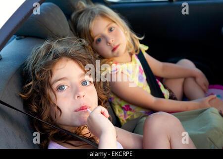 little girls inside car eating candy stick - Stock Photo