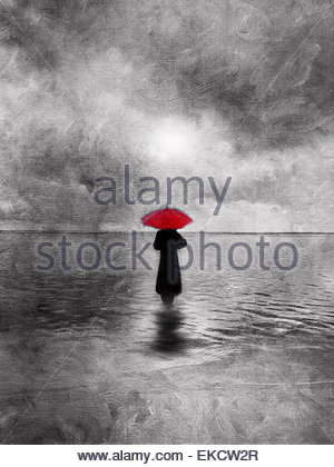Atmospheric solitary woman with red umbrella wading in water - Stock Photo