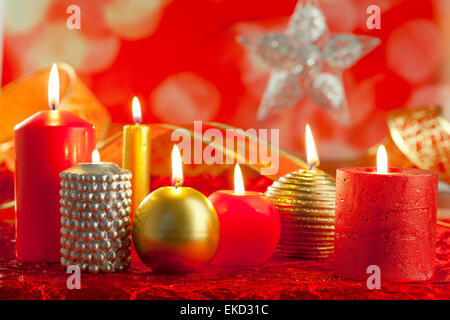 Christmas card candles red and golden in a row - Stock Photo
