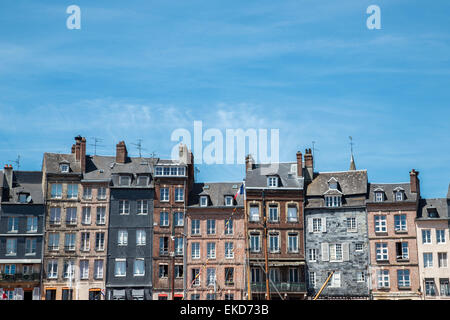 Honfleur Harbour Town, Historic waterside buildings of irregular sizes against blue sky, Normandy France - Stock Photo