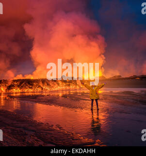 Woman standing by Glowing lava from the eruption at the Holuhraun Fissure, near the Bardarbunga Volcano, Iceland - Stock Photo
