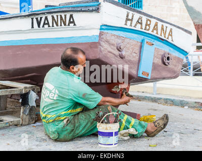 a middle age cuban man sits on the ground as he repairs the