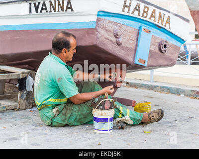 A middle-age Cuban man sits on the ground as he repairs the propeller on his boat in Havana, Cuba. - Stock Photo