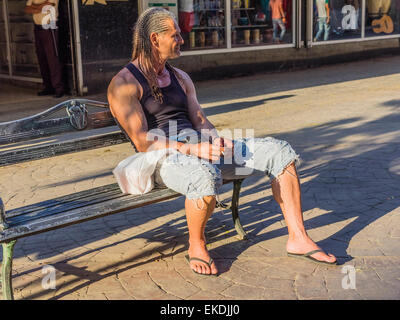A 30s Cuban male with dreadlocks sits on a city bench on a sidewalk in Havana and smokes a cigarette in late afternoon - Stock Photo