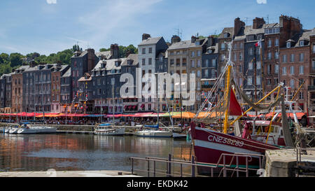 Boats moored in harbour next to quayside historic buildings, cafes and restaurants,  Honfleur Town, Normandy France - Stock Photo