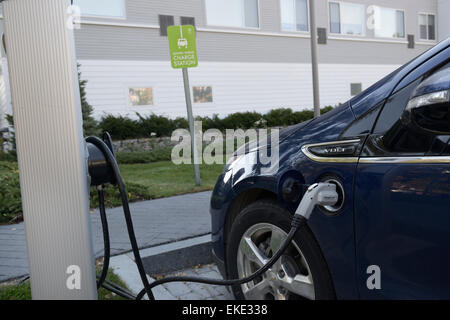 Electric car charging at a hotel parking lot charging station - Stock Photo