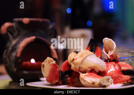Jonah crab claws cracked open, showing succulent meat on a plate, with candle light and defocsed wine glass in fine - Stock Photo
