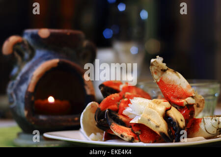 Jonah crab claws showing succulent meat on a plate, with candle light and defocsed flute glass in fine dining settings. - Stock Photo
