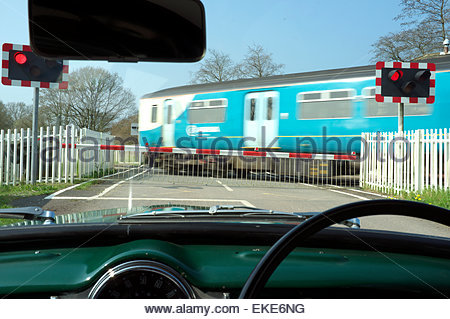 Passenger train passing over a level crossing, as seen thru the windscreen of a Morris Minor car. Awre, Gloucestershire, - Stock Photo