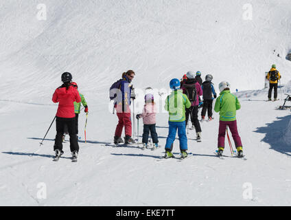 Children skiing with a family group getting ready to descend a ski run in Verbier in the Swiss alps - Stock Photo