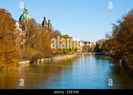 Munich, Isar river on autumn with red leaves and the view of the St. Luke's church domes - Stock Photo