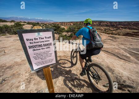 Moab, Utah, USA. 5th Apr, 2015. Mountain biker TIM LANE riding past a sign that says beware 'Scouts shooting range' - Stock Photo