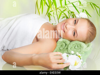 Relaxed female lying down in spa salon on massage table, enjoying nice beauty procedure, healthy lifestyle, wellness - Stock Photo