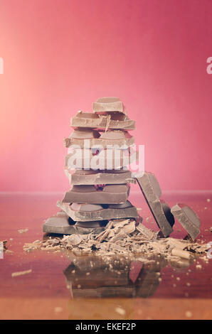 Stack of chocolate on reflective glass against red background with applied retro vintage style filters and added - Stock Photo