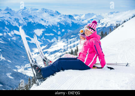 Young skier sitting on the hill - Stock Photo