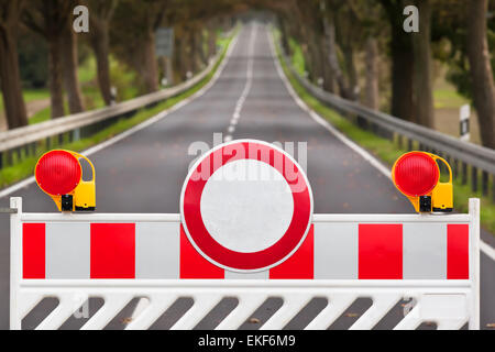 Red and white colored street barrier at long empty road - Stock Photo