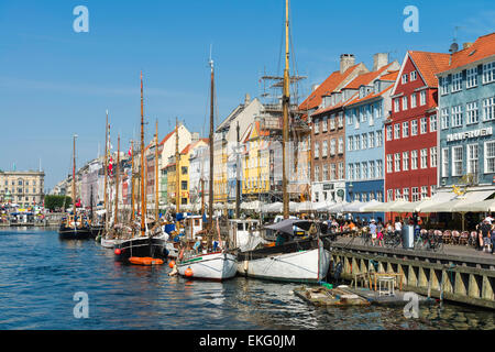 Colourful façades of 17th and 18th century townhouses and historic ships line Nyhavn canal, Copenhagen waterfront, - Stock Photo