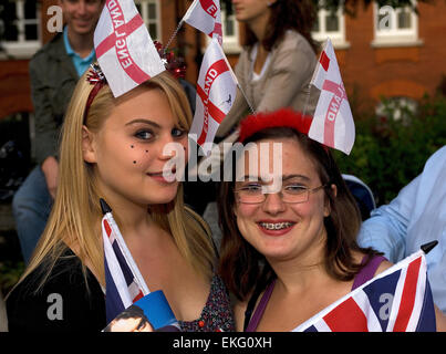Two young women, suitably got up with George flags, wait outside the Albert Hall for the Last Night of the Proms. - Stock Photo