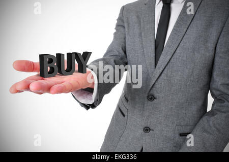 a young businessman wearing a gray suit shows the word buy, three-dimensional, in the palm of his hand - Stock Photo