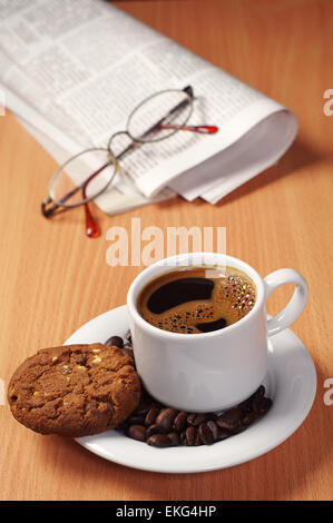 Coffee cup with chocolate cookie and newspaper on desk - Stock Photo