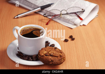 Cup of hot coffee with chocolate cookie and newspaper on table - Stock Photo