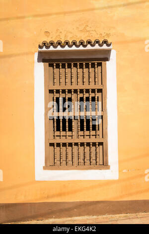 Cuba Trinidad sand coloured colored house detail wooden window shutters bars - Stock Photo
