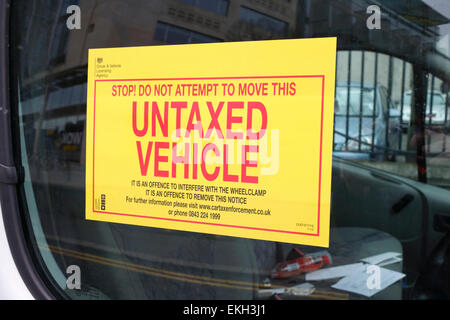 warning sticker attached to window of vehicle clamped for unpaid vehicle tax - Stock Photo