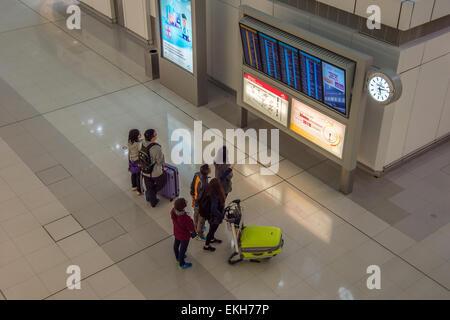 Passengers looking at departure display at Hong-Kong airport
