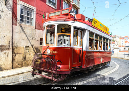 Traditional trams on medieval street of Alfama, ancient district of Lisbon, Portugal. - Stock Photo