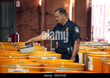 U.S. Customs and Border Patrol agent conducts search on barrel containers with the use of an electronic device called - Stock Photo