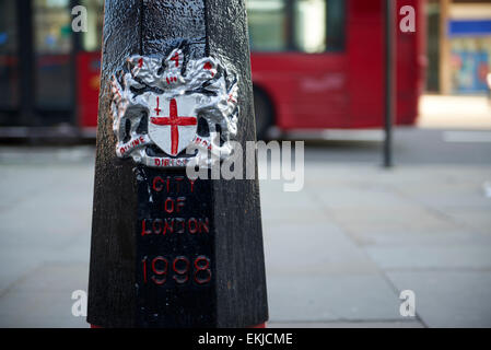 LONDON, UK - APRIL 06: Detail of black City of London bollard featuring its coat of arms, with read of red bus in - Stock Photo