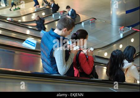 people using mobile phones on moving escalator, canary wharf, london, england - Stock Photo