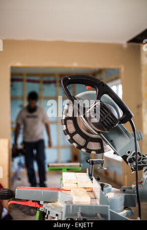 Miter Saw on a construction site with a worker in background - Stock Photo