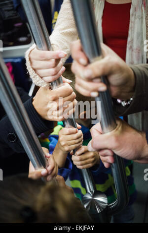 Lot of Hands Holding at the same Pole in a Subway Wagon - Stock Photo