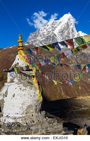 Sherpa prayer flags, attached to a Buddhist stupa (chorten) fly in teh weind in front of distant snowy peaks - Dingboche - Stock Photo