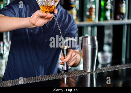 Barman makes cocktail on the counter - Stock Photo