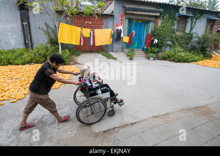 Middle aged woman pushes senior in wheel chair as pass by drying corn and laundry, Anyang, Henan Province, China. - Stock Photo