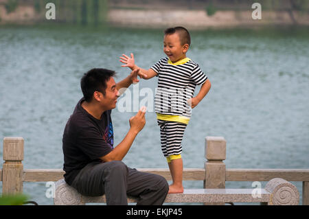 Father and son act out sword fight they watched at the Emperior's Palace Park, Kaifeng, Henan Province, China - Stock Photo