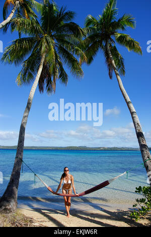 Young woman in bikini standing by the hammock between palm trees, Ofu island, Vavau group, Tonga - Stock Photo