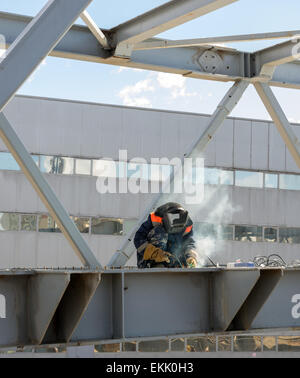 worker welder welds the steel bridge construction - Stock Photo