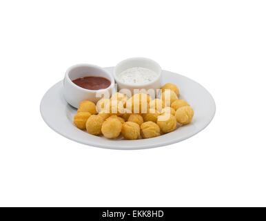Potato balls with sauce on a dish on white background - Stock Photo