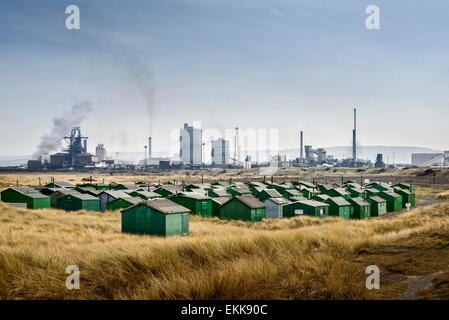 Fishermen's huts at South Gare in Redcar with the Sahaviriya Steel Industries UK (SSI) Steel Plant in the background. - Stock Photo