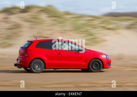 Volkswagen car speeding on the sandy beach at Southport, Merseyside, UK . 11th April, 2015.  Activities, sports, - Stock Photo