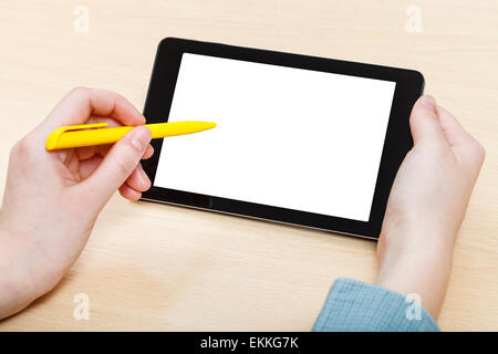 businessman touches by pen of tablet PC with cutout screen at office desk - Stock Photo
