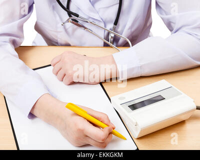 doctor measures blood pressure during appointment isolated on white - Stock Photo
